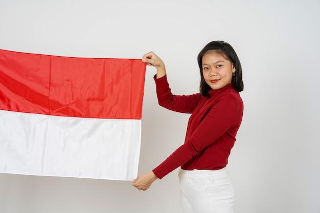Belle femme indonésienne tenant le drapeau de l'indonésie