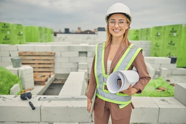 Belle femme ingénieur civil à lunettes debout sur un chantier
