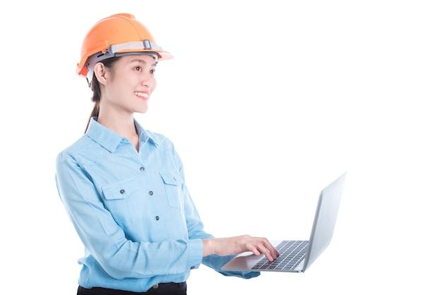 Belle femme ingénieure portant un casque et à l'aide d'un ordinateur portable