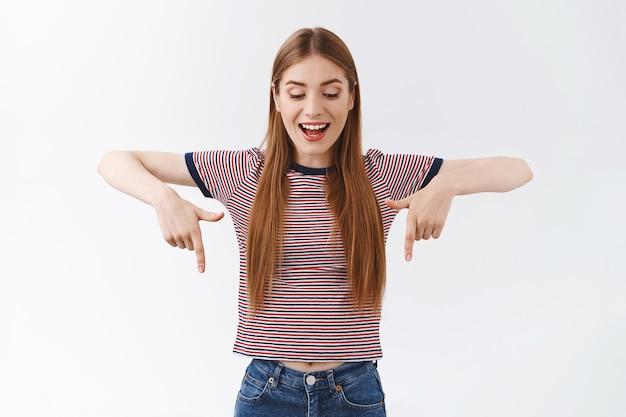 Belle femme intriguée et excitée aux cheveux blonds, porte un t-shirt à rayures, regarde vers le bas, se divertit, ouvre la bouche avec enthousiasme, observe un événement génial, se tient intéressée sur un mur blanc