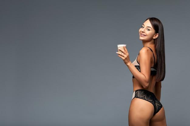 Belle femme italienne avec du café en lingerie, sur fond gris avec espace copie.