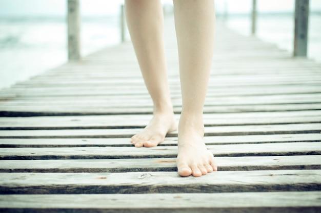 Belle femme jambes et pieds marchant sur le pont en bois