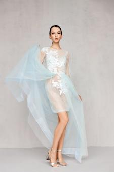 Belle femme jetant l'ourlet de la robe transparente