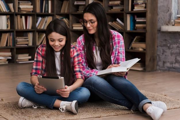 Belle femme et jeune fille à la bibliothèque