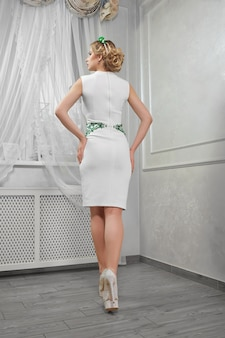 Une belle femme, jeune fille blonde dans une courte robe blanche, sur des talons,