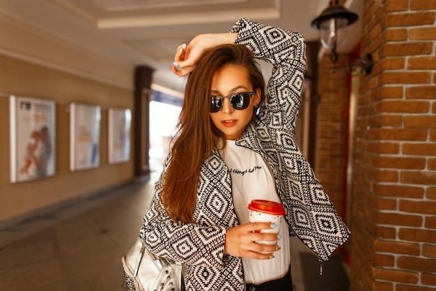 Belle femme jeune mannequin avec un café dans des vêtements à la mode avec une veste pose dans la ville