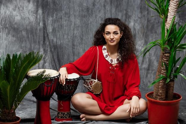 Belle femme jouant du tambour dans les plantes tropicales sur mur gris