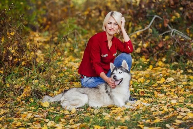 Belle femme joue avec un chien husky dans la forêt d'automne