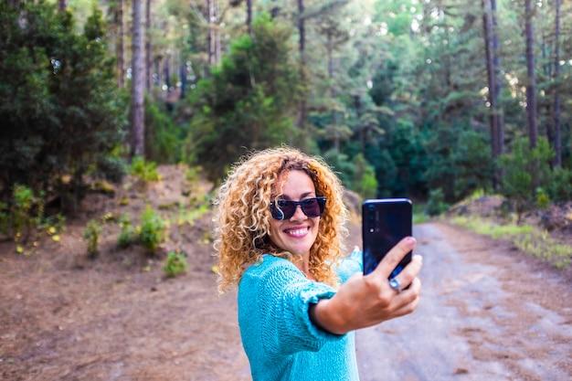 Une belle femme joyeuse adulte prend une photo de selfie dans la forêt, profitant des arbres et de la nature en plein air