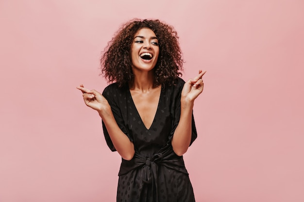 Belle femme joyeuse avec une coiffure élégante et une peau bronzée dans des vêtements sombres à la mode en détournant les yeux et en croisant les doigts