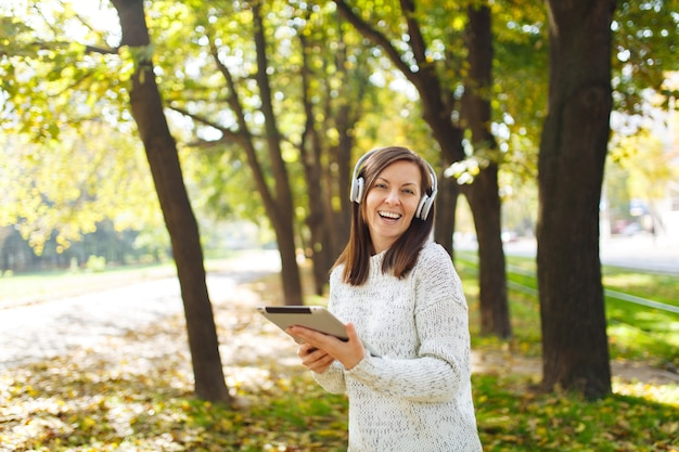 La belle femme joyeuse et joyeuse aux cheveux bruns en pull blanc avec une tablette écoutant de la musique dans les écouteurs blancs dans le parc de l'automne par une chaude journée. automne dans la ville.