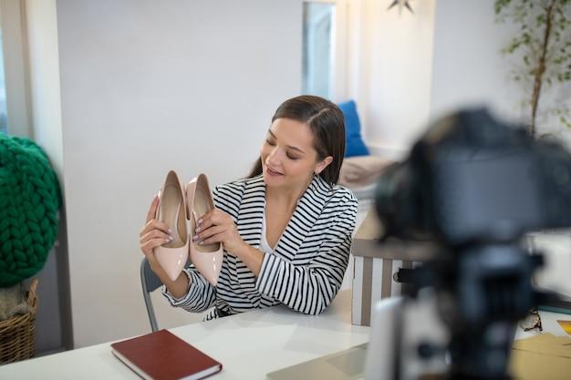 Belle femme joyeuse tenant une paire de chaussures devant la caméra tout en ayant un cadeau pour eux