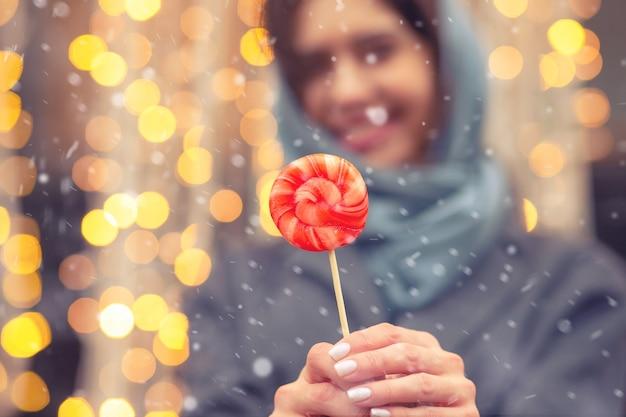 Belle femme joyeuse vêtue d'un manteau bleu gris et d'une écharpe chaude tenant des bonbons au caramel dans la rue pendant les chutes de neige. espace pour le texte