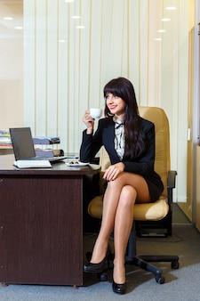 Belle femme en jupe courte, buvant du café au bureau