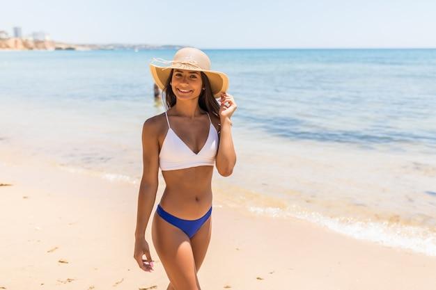 Belle femme latine sur la plage s'enfuyant tout en regardant la caméra. portrait de femme bronzée heureuse souriant avec la mer en arrière-plan.