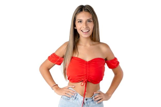 Belle femme latine avec ses mains sur sa taille et regardant droit devant elle souriante sur un fond blanc pur.