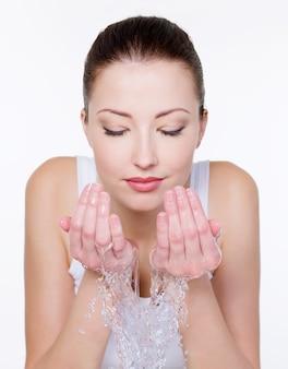 Belle femme lave son visage isolé sur blanc