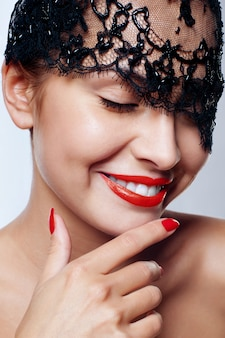 Belle femme avec des lèvres rouges et masque de dentelle sur ses yeux.