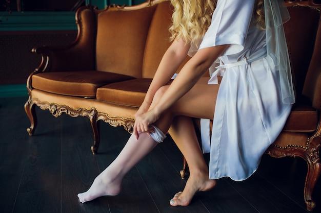 Belle femme en lingerie blanche assise sur le lit dans sa chambre et chaussant ses bas.
