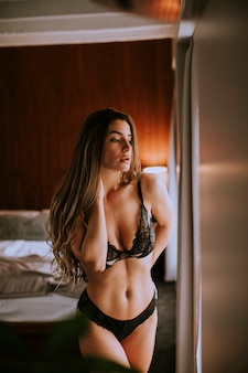 Belle femme en lingerie regardant par la fenêtre dans son bel appartement