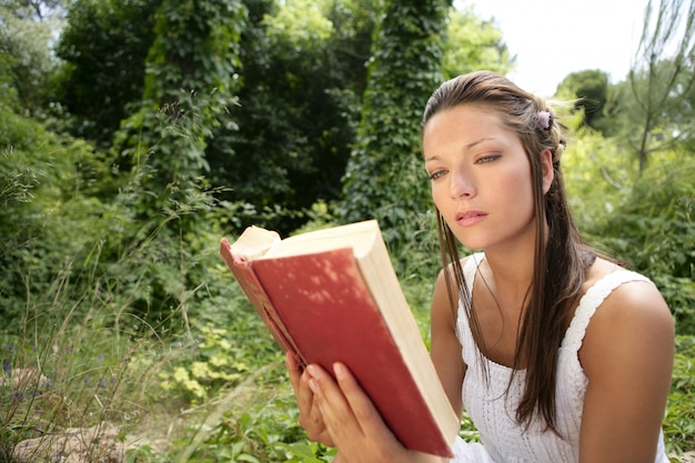 Belle femme lisant un livre dans la forêt, nature