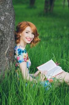 Belle femme lisant un livre dans le jardin de printemps