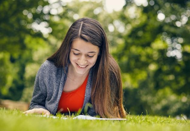 Belle femme lisant un livre dans la nature. jeune étudiant attrayant en robe rouge étudiant et lisant un livre. détendez-vous, reposez-vous, concept d'éducation, loisirs.