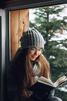 Belle femme lisant un livre dans un pull assis à la maison près de la fenêtre