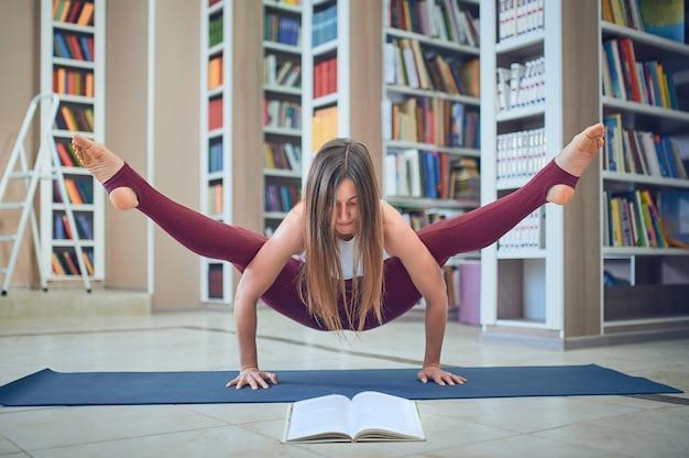 Belle femme lisant un livre et pratique le handstand yoga asana tittibhasana