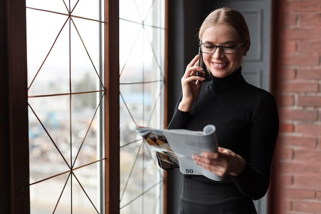 Belle femme lisant un magazine et parlant au téléphone