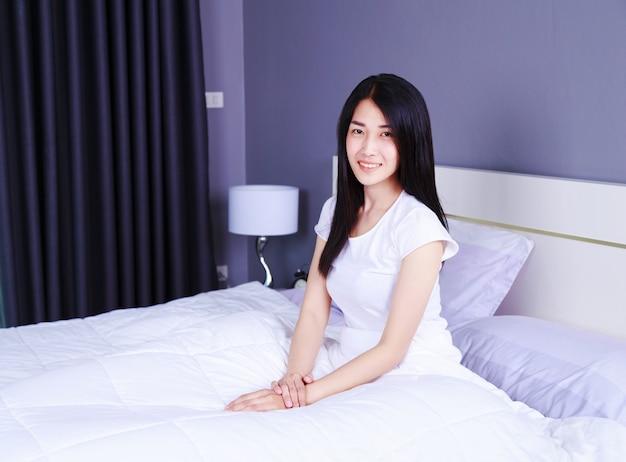 Belle femme sur le lit dans la chambre