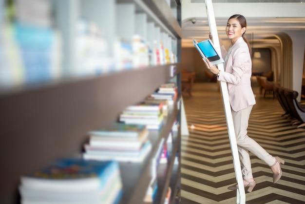 Belle femme lit des livres dans la bibliothèque