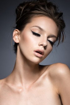 Belle femme avec de longs cils et une peau parfaite