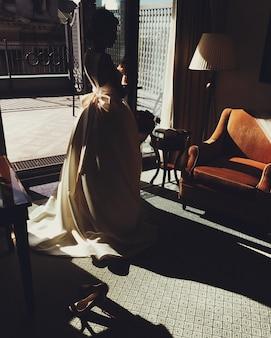 Belle femme en longue robe blanche, se dresse dans une ancienne salle confortable près du fauteuil et de la lampe, se sent détendue