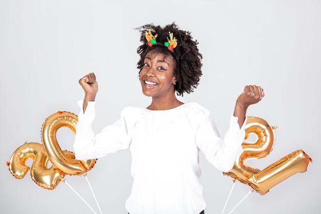 Belle femme lors d'une fête du nouvel an: jouer avec des ballons d'or numéros 2021