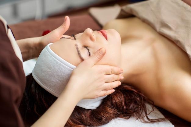 Belle femme lors d'un massage du visage dans un salon spa.