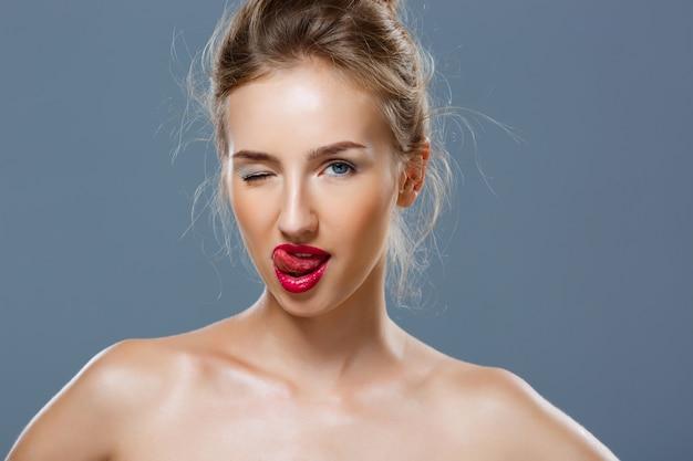 Belle femme ludique blonde avec un maquillage lumineux clin de œil, montrant la langue