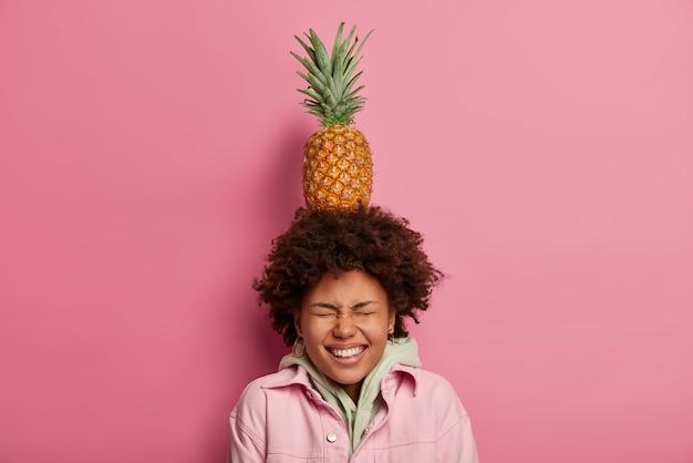 Belle femme ludique avec une coiffure afro, équilibre avec de l'ananas exotique sur la tête, le visage louche, a le sourire à pleines dents, vêtue d'un sweat à capuche, pose contre le mur rose pastel. dame joue avec des fruits mûrs