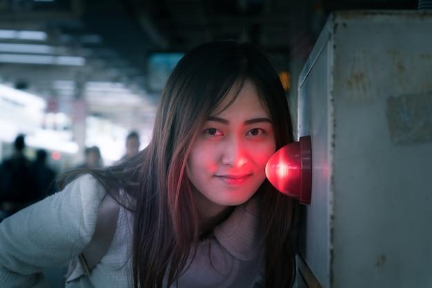 Belle femme avec la lumière de la sirène rouge