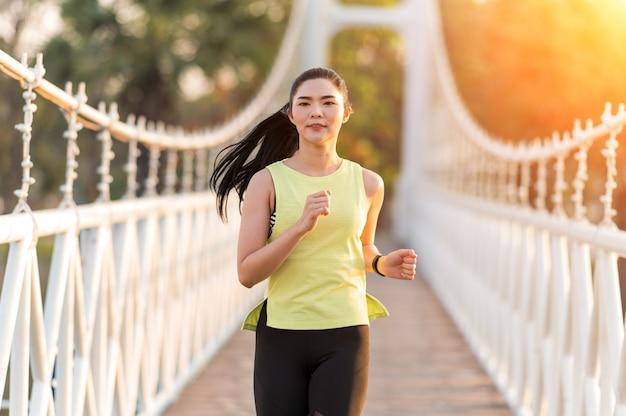 Une belle femme lumineuse qui court sur un pont en bois
