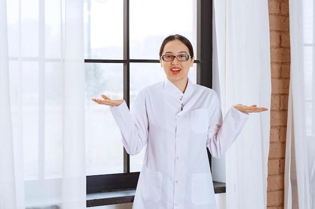 Belle femme à lunettes et blouse de laboratoire debout près de la fenêtre et haussant les épaules.