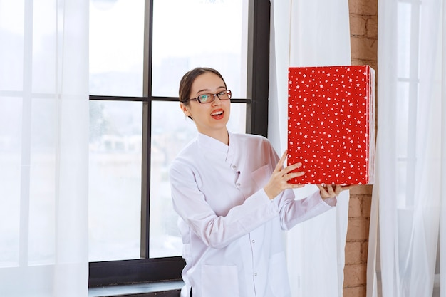 Belle femme avec des lunettes en blouse de laboratoire tenant une grande boîte présente près de la fenêtre.