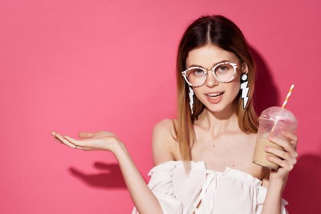 Belle femme avec des lunettes boucles d'oreilles fashion fond rose
