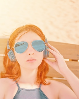 Belle femme à lunettes, écouter de la musique sur la plage.