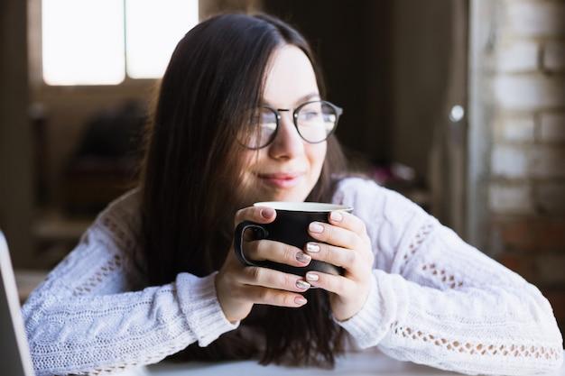 Belle femme à lunettes est assise tenant une tasse de café et à l'aide d'un ordinateur portable