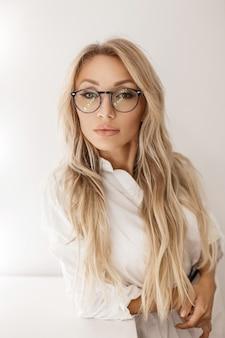 Belle femme avec des lunettes à la mode dans l'élégante chemise blanche près du mur gris