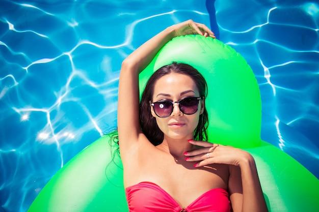 Belle femme à lunettes de soleil allongée sur un matelas pneumatique dans la piscine
