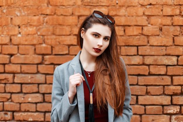 Belle femme avec des lunettes de soleil dans un manteau près d'un mur de briques vintage