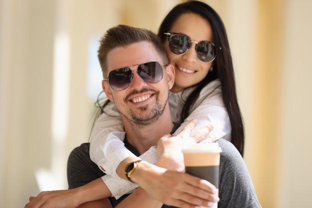Belle femme à lunettes de soleil embrasse l'homme derrière le cou et tient le verre en carton avec du café à la main.