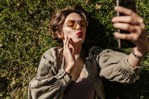Belle femme en lunettes de soleil rondes et veste se trouve sur l'herbe et souffle à l'extérieur. jeune femme aux cheveux courts prenant selfie à l'extérieur.